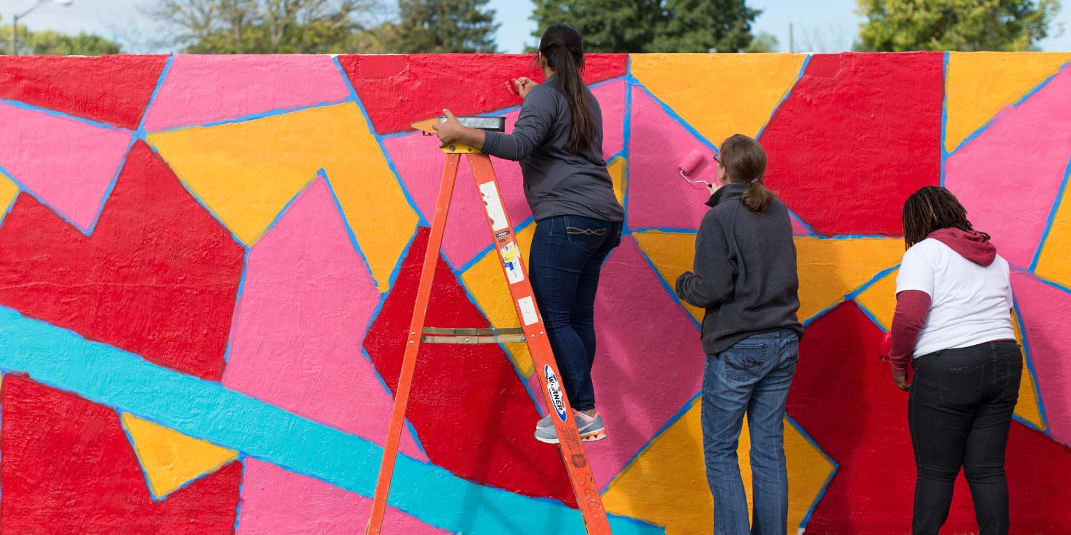 Three students paint an exterior wall with bright colors as part of a community service project.
