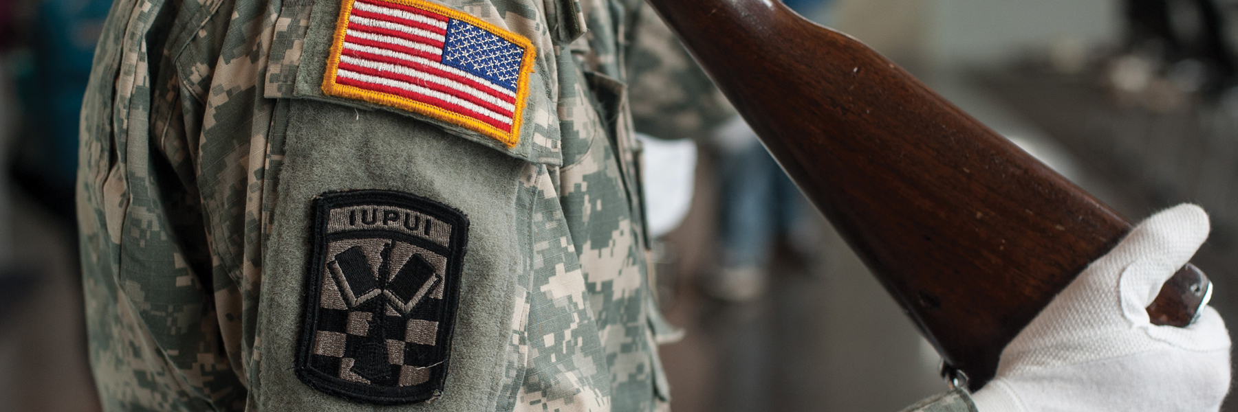 Closeup shot of student wearing military camouflage uniform with IUPUI badge and flag badge on shoulder.