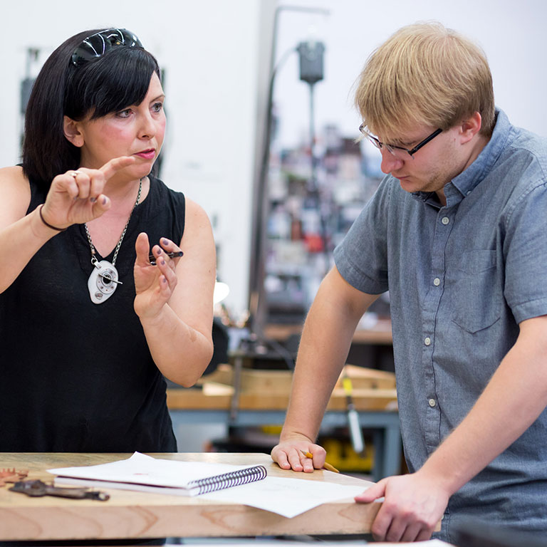 A student and instructor talking in an art class