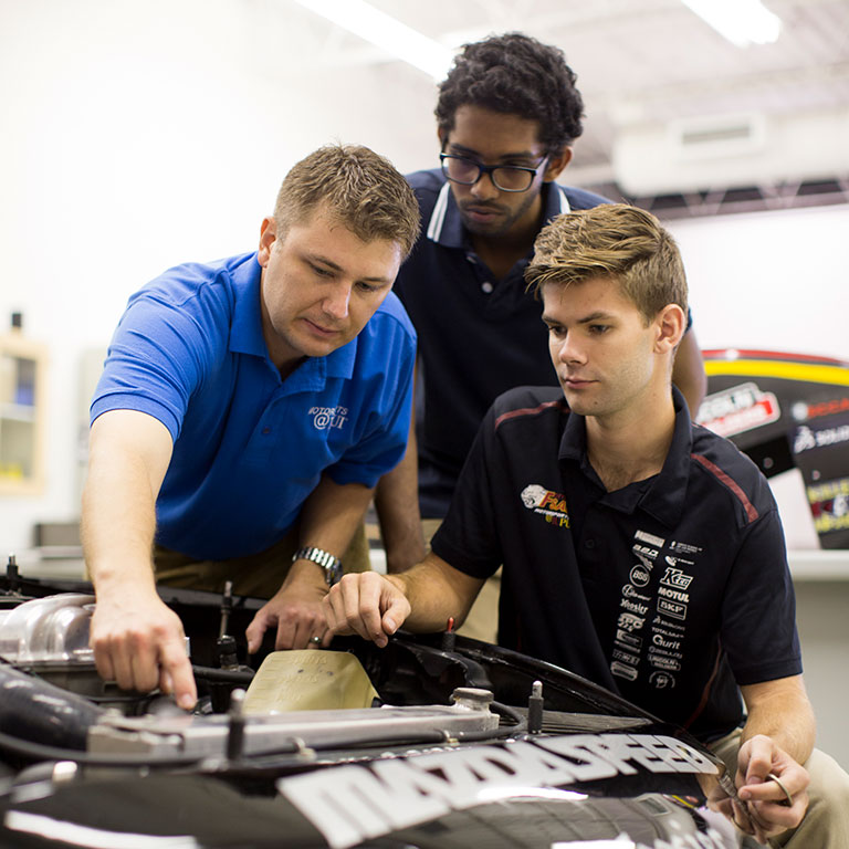 Two male students listening to an instructor in the Engineering Motorsports garage