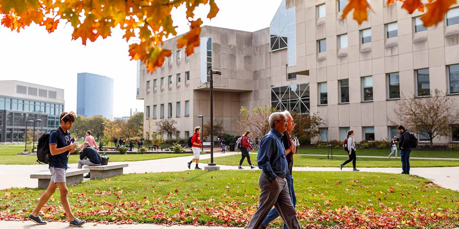 People stroll through the IUPUI campus on an autumn day.
