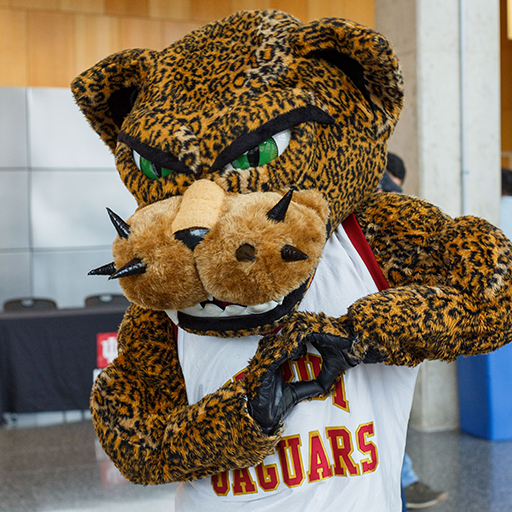 Jawz the Jaguar, IUPUI's mascot, makes a heart with his hands.