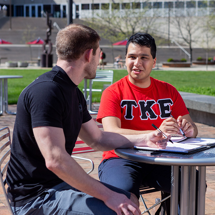 Two males sitting at a metal table outside of IUPUI's University Library. Both are holding pens and have paper in front of them. The male student on the right has a red shirt that prominently displays the fraternity TKE.