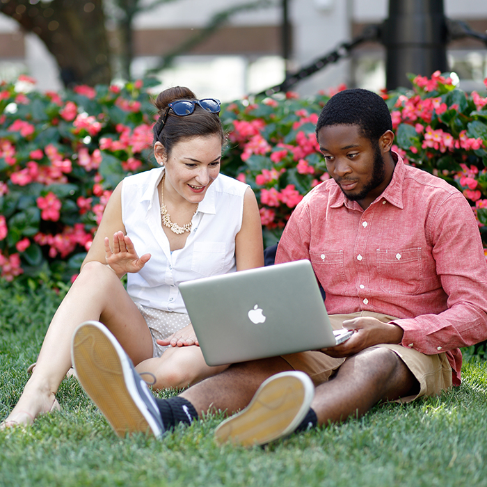 Two students sitting on the gras near Monument Circle in Downtown Indianapolis. The male (on the right) is holding a laptop, while the female (on the left) looks at the screen with him.