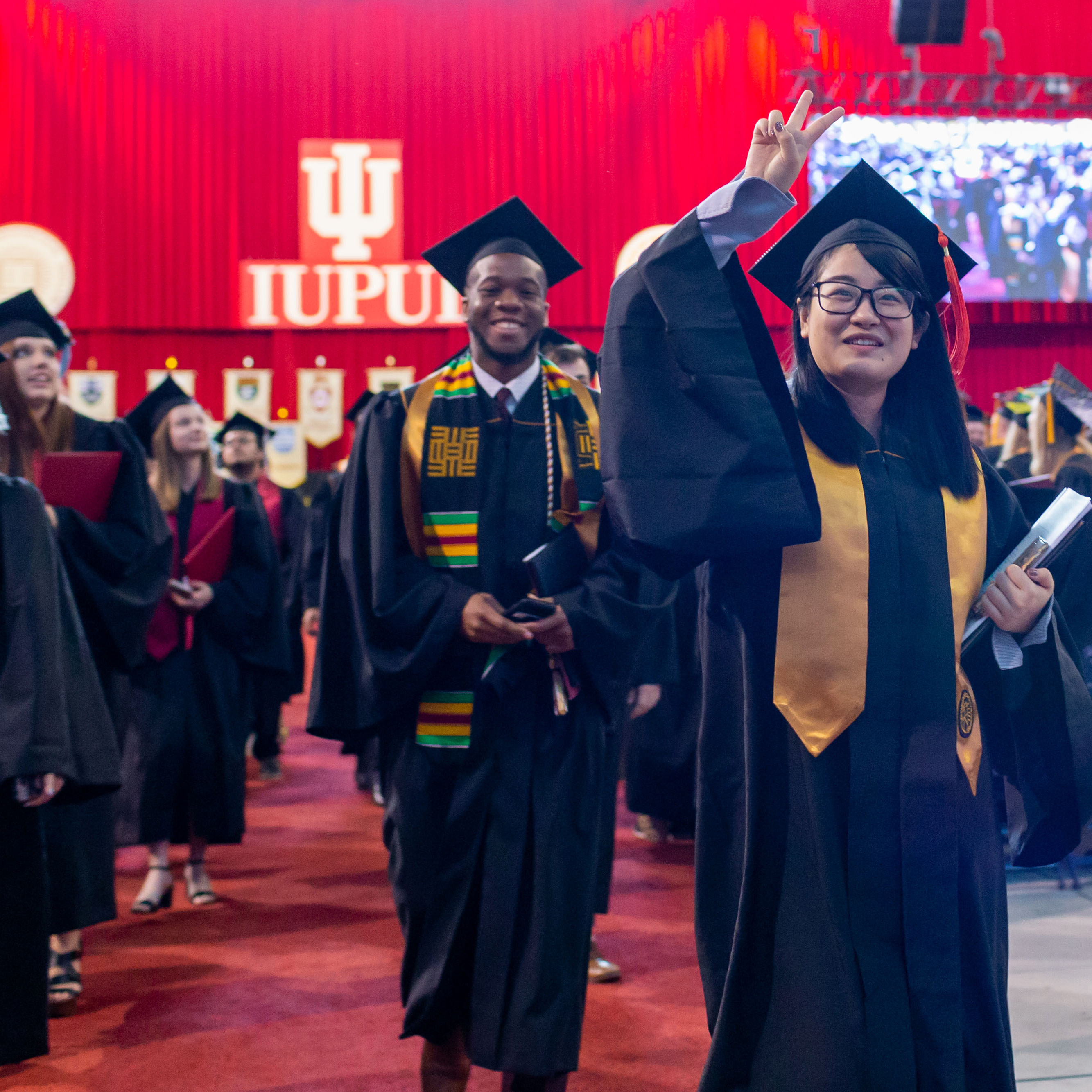 Students participating in IUPUI's commencement. The student in the forefront is female has a gold stole and black robes.