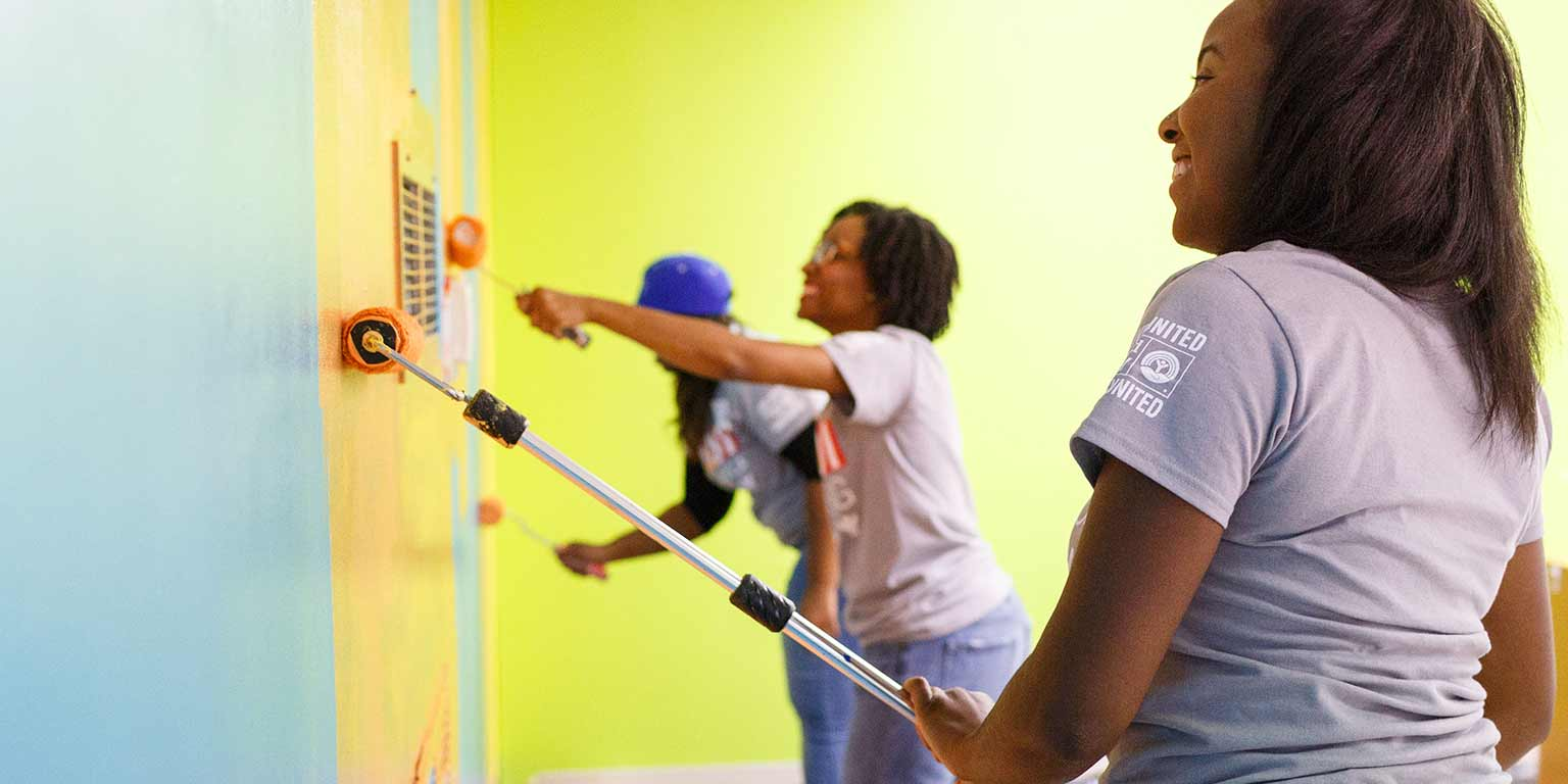 Students repaint a wall as part of a community service project.