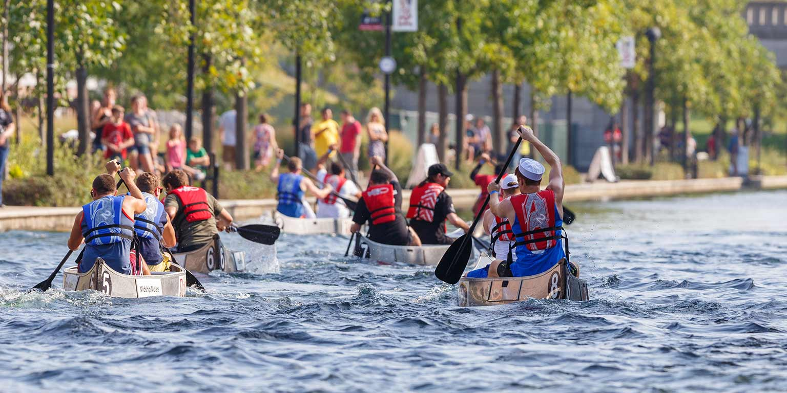 People paddle canoes down the canal at the annual IUPUI Regatta.