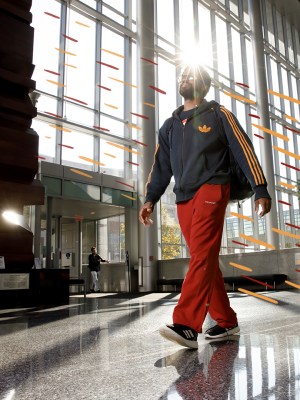 An IUPUI student walking across the campus center in Jaguar gear.