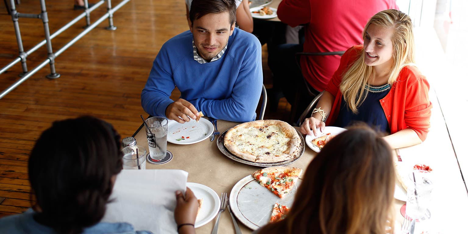 A group shares a pizza at a restaurant.